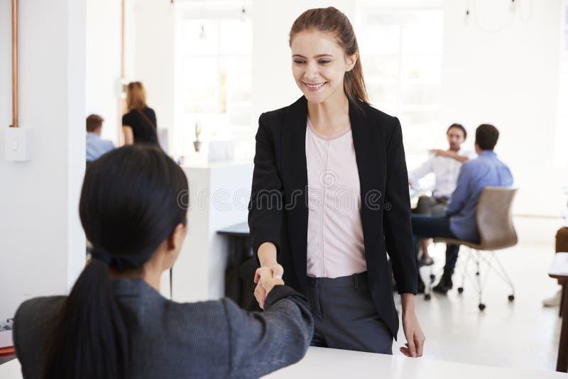 Zwei Frauen, die Hände bei einer Sitzung in einem Bürogroßraum rütteln stockbilder