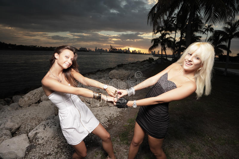 Zwei Frauen, die Hände und das Schwingen anhalten stockbilder