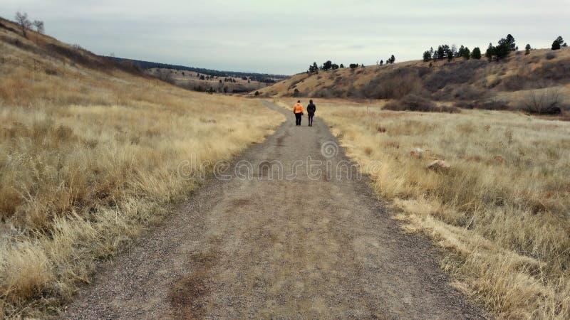 Zwei Frauen, die hinunter einen Schotterweg gehen stockfotografie