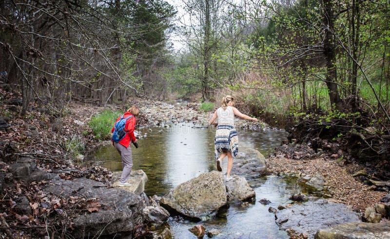 Zwei Frauen, die im Wald über einem Wasserstrom wandern stockfotografie