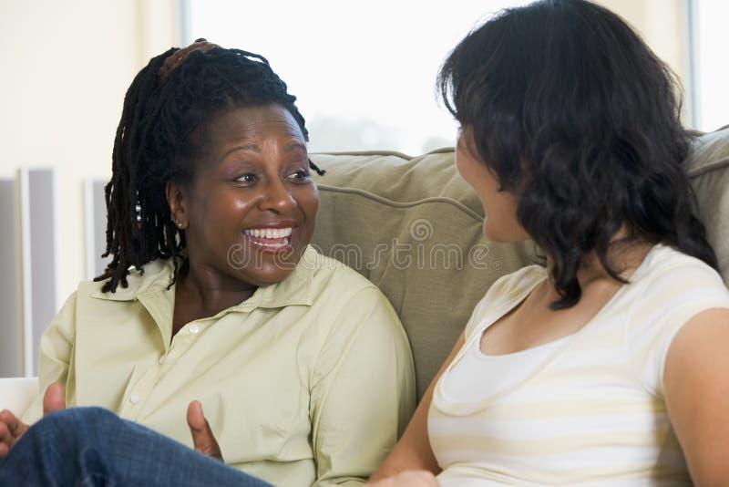 Zwei Frauen, die im Wohnzimmer und im Lächeln sprechen lizenzfreie stockbilder