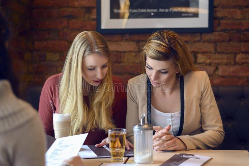 Zwei Frauen, die Menüs in einem Restaurant wiederholen stockfoto