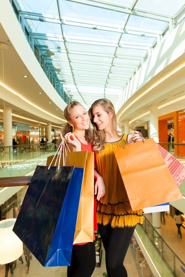 Zwei Frauen, die mit Taschen im Mall kaufen lizenzfreies stockfoto