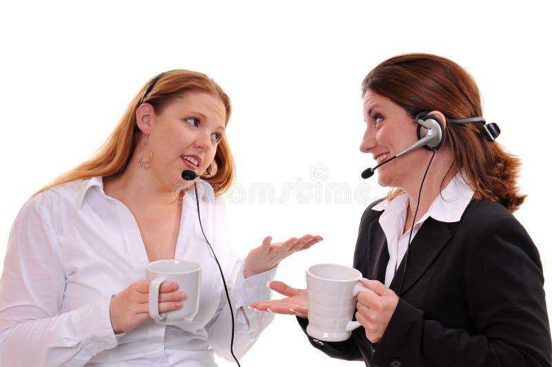 Zwei Frauen, die mit tragenden Kopfhörern plaudern lizenzfreie stockfotos