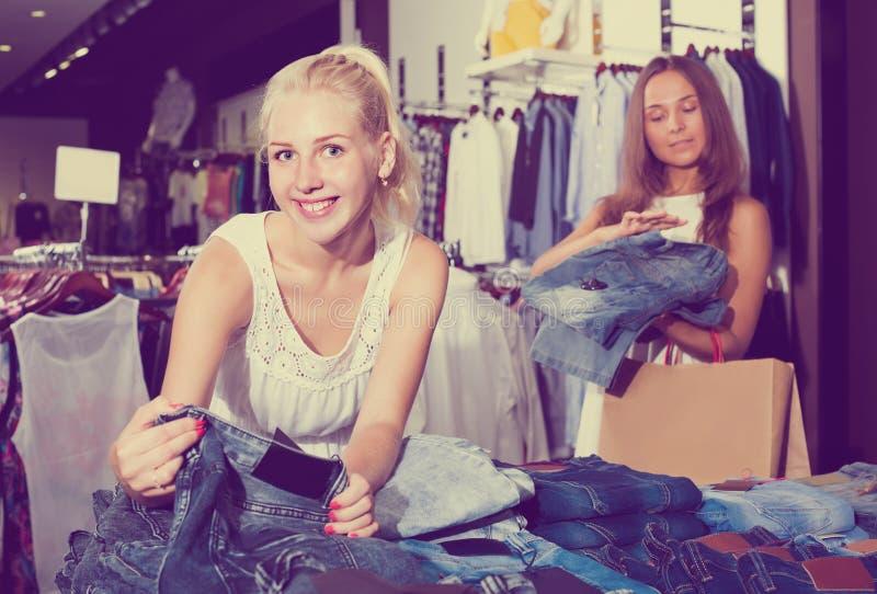Zwei Frauen, die in Mode neue Abteilung der Jeans auswählen lizenzfreies stockbild