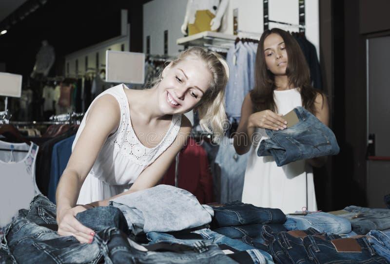 Zwei Frauen, die in Mode neue Abteilung der Jeans auswählen lizenzfreie stockfotos