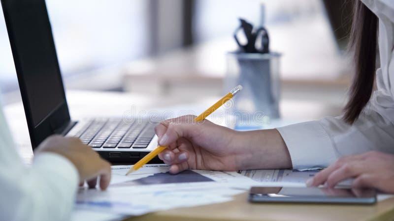 Zwei Frauen, die Projekt besprechen und zusammen an Papieren im Firmenbüro arbeiten stockbild