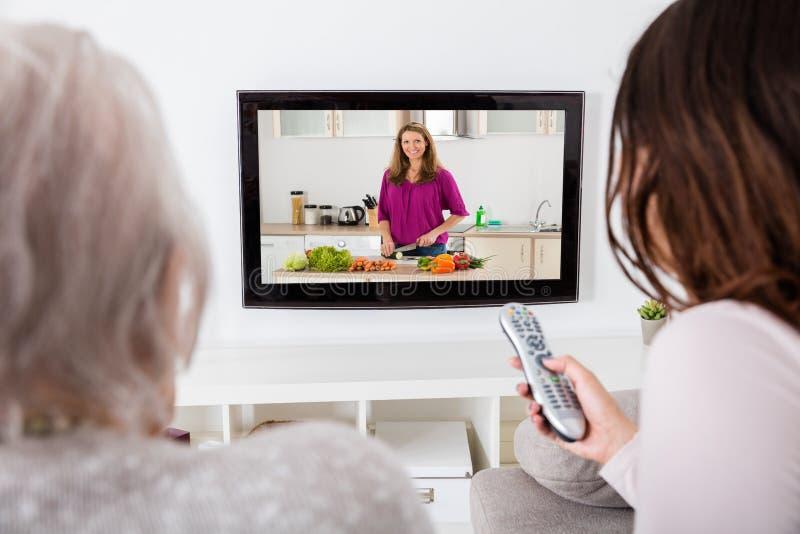 Zwei Frauen, die Show im Fernsehen kochend aufpassen lizenzfreies stockfoto