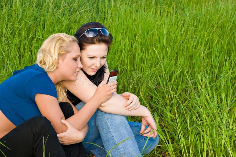 Zwei Frauen, die sms lesen stockbilder