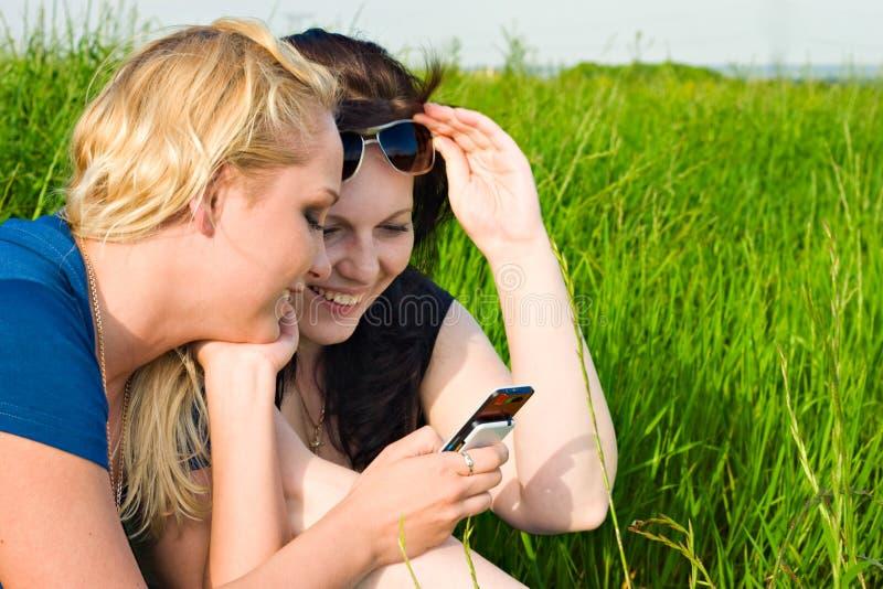Zwei Frauen, die sms lesen stockfotos