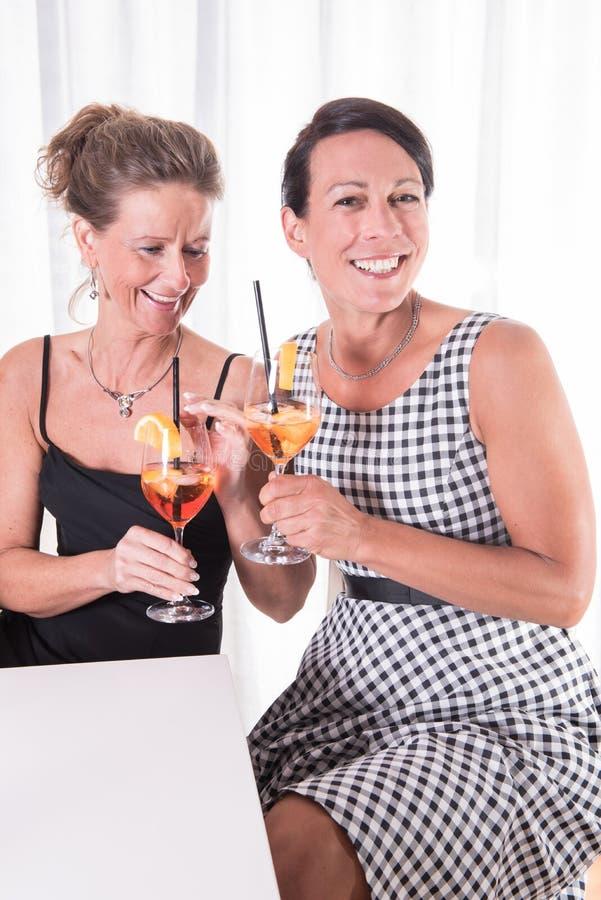 Zwei Frauen, die sprechen und etwas trinken stockfoto