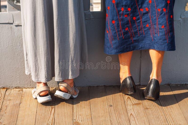 Zwei Frauen, die an stehen, gehen auf den Zehen Neugierkonzept stockfotografie