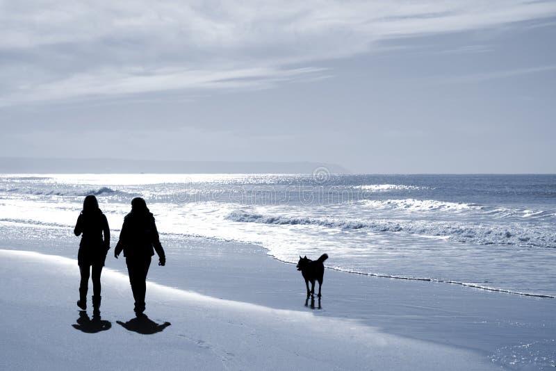 Zwei Frauen, die am Strand gehen lizenzfreie stockfotos