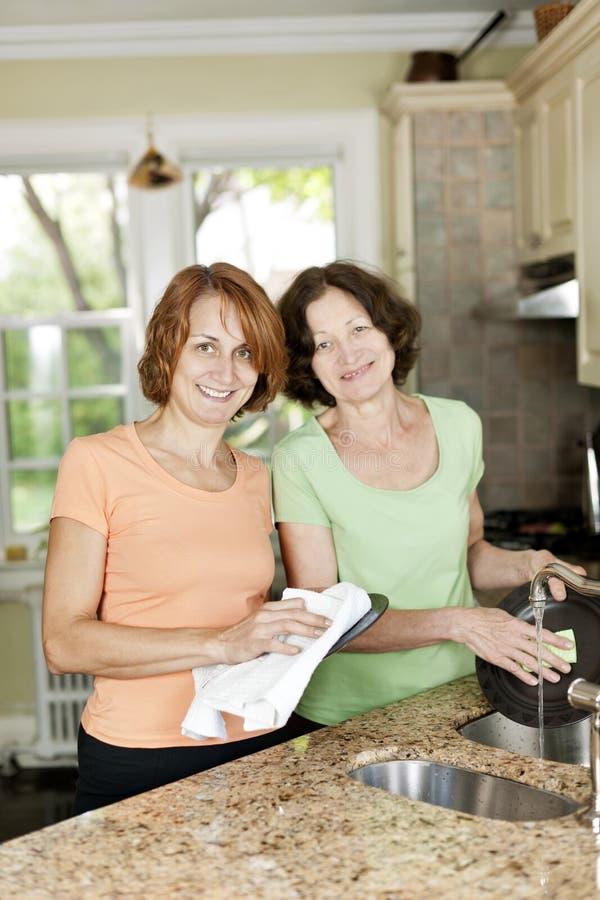 Zwei Frauen, die Teller in der Küche tun lizenzfreie stockbilder