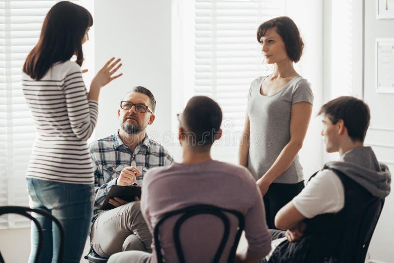 Zwei Frauen, die w?hrend der Gruppentherapie mit Psychologen stehen und sprechen stockfoto