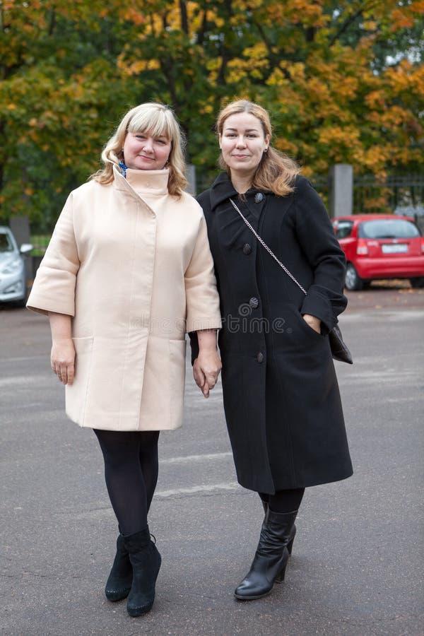 Zwei Frauen, die zusammen nahe städtischem Herbstpark, Ganzaufnahme stehen stockfotos