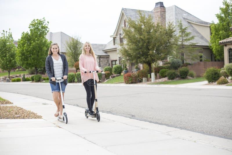 Zwei Frauen, die zusammen Roller in eine Nachbarschaft reiten stockfotografie