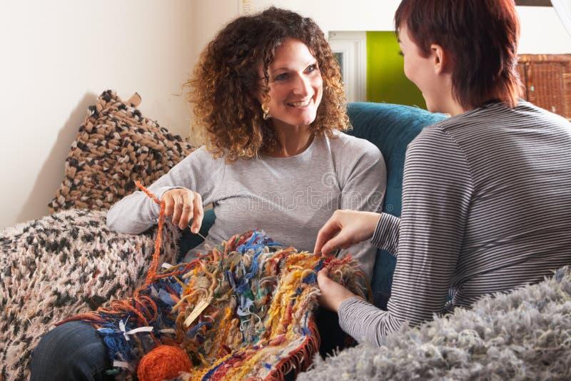 Zwei Frauen, die zusammen zu Hause stricken lizenzfreie stockbilder