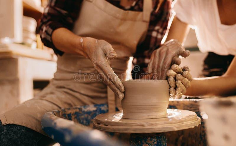 Zwei Frauen an einer Tonwarenwerkstatt, die Tongefäße herstellt stockbild