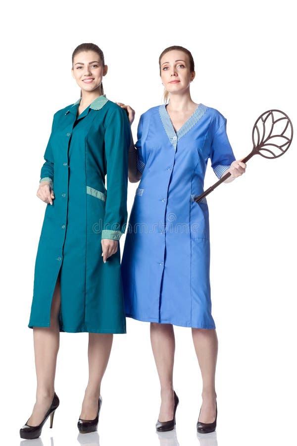 Zwei Frauen im Kostüm der Reinigungsfrau stockbild