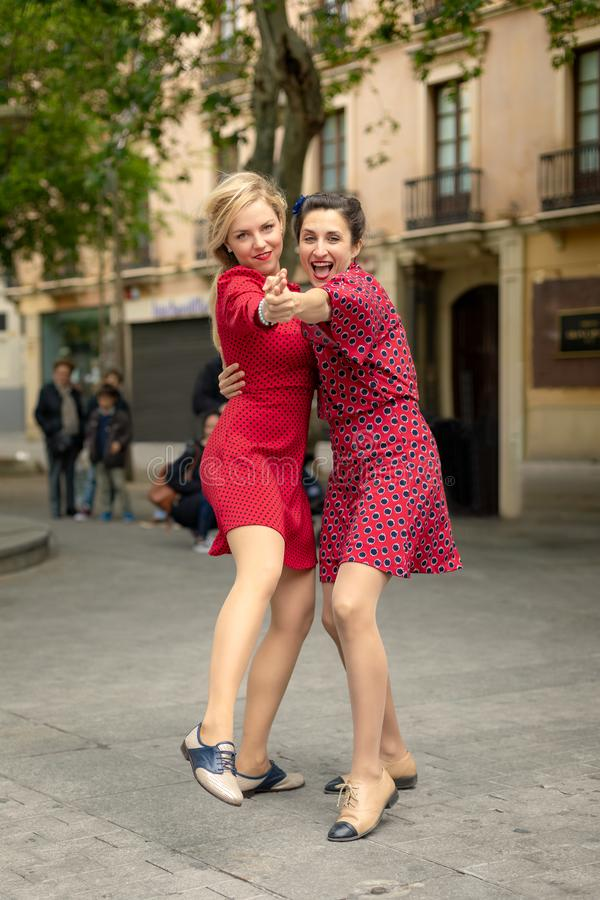 Zwei Frauen im roten Tanzen umfassten gl?cklich in der Stra?e lizenzfreie stockfotografie