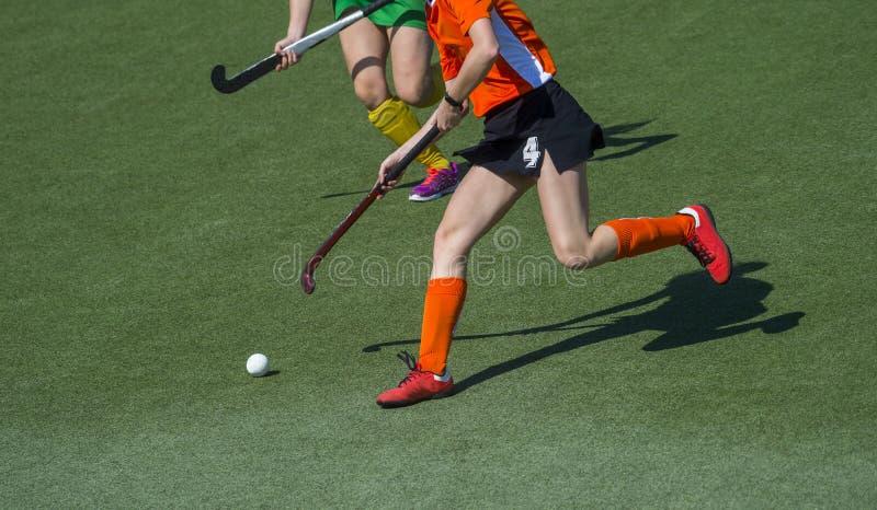 Zwei Frauen k?mpfen zur Steuerung des Balls w?hrend des Hockeyspiels stockbilder