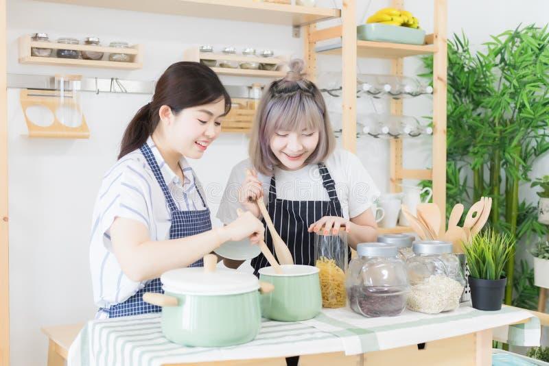 Zwei Frauen l?cheln, schmecken Nahrung und kochen auf einer Tabelle voll von K?chenger?ten Es gibt einen Hintergrund von Würzen lizenzfreie stockfotos