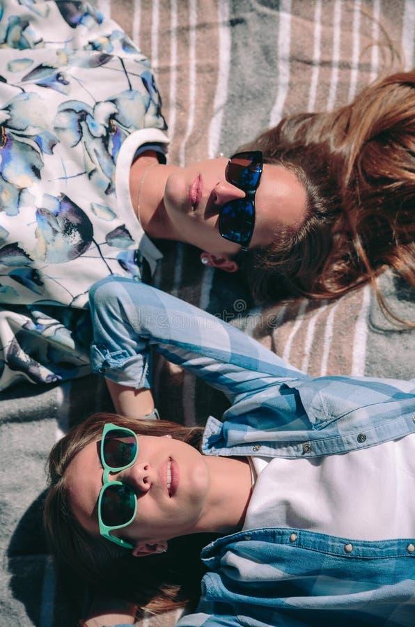 Zwei Frauen mit der Sonnenbrille, die ein sunbath nehmend liegt stockbild