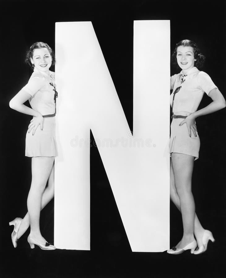 Zwei Frauen mit enormem Buchstaben N (alle dargestellten Personen sind nicht längeres lebendes und kein Zustand existiert Liefera lizenzfreies stockbild