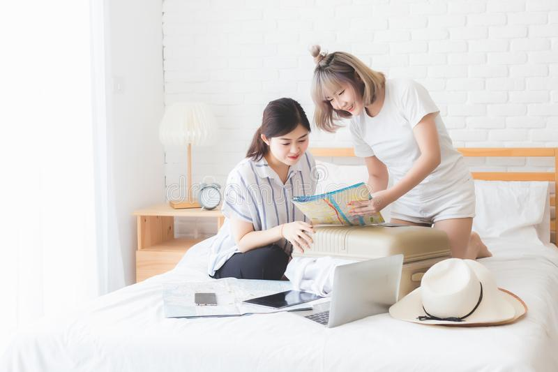Zwei Frauen planen eine Reise und helfen, Gepäck vorzubereiten, um im Ausland auf ein Bett mit Hüten, Karten, Laptops und Tablett lizenzfreie stockfotos