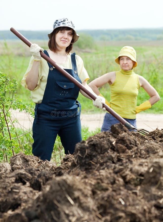Zwei Frauenarbeiten mit Düngemittel stockfoto
