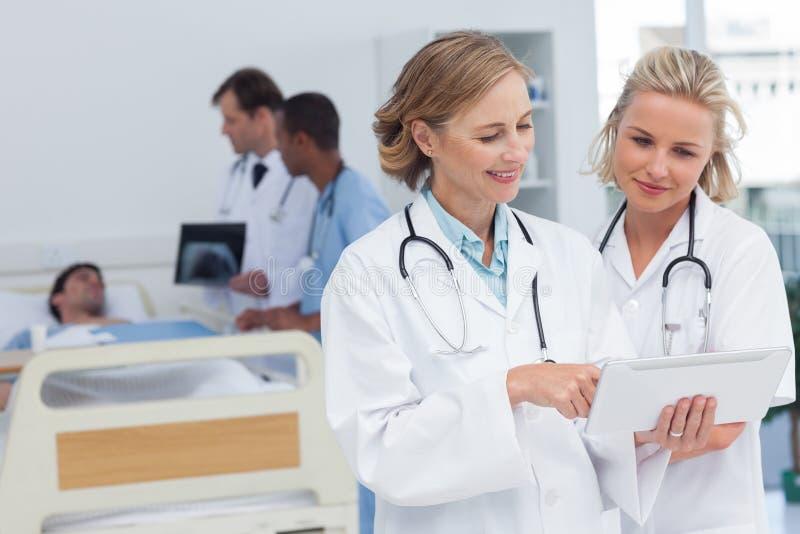 Zwei Frauendoktoren, die Tablette betrachten lizenzfreie stockfotografie
