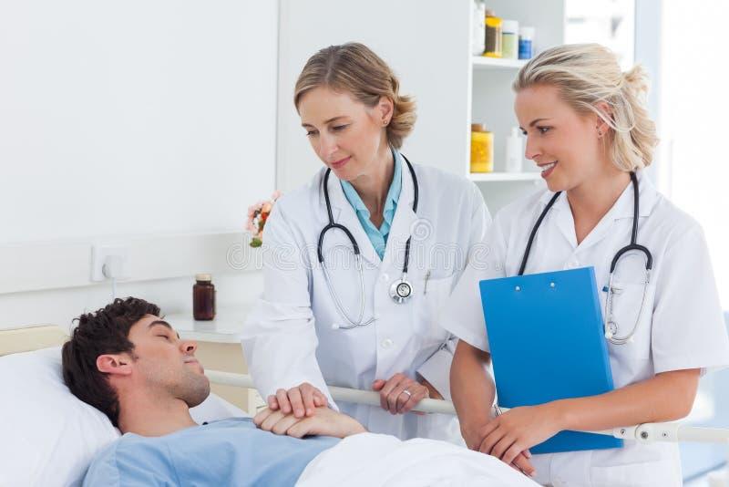 Zwei Frauendoktoren, die um einem Patienten sich kümmern stockfotos