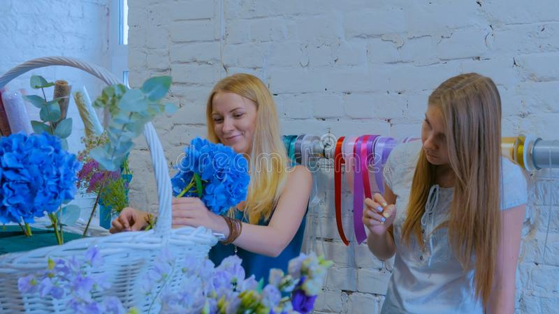 Zwei Frauenfloristen, die gro?en Blumenkorb mit Blumen am Blumenladen machen lizenzfreies stockbild