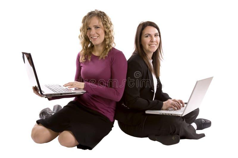 Zwei Frauenrückseiten zusammen auf Computern lizenzfreie stockfotografie