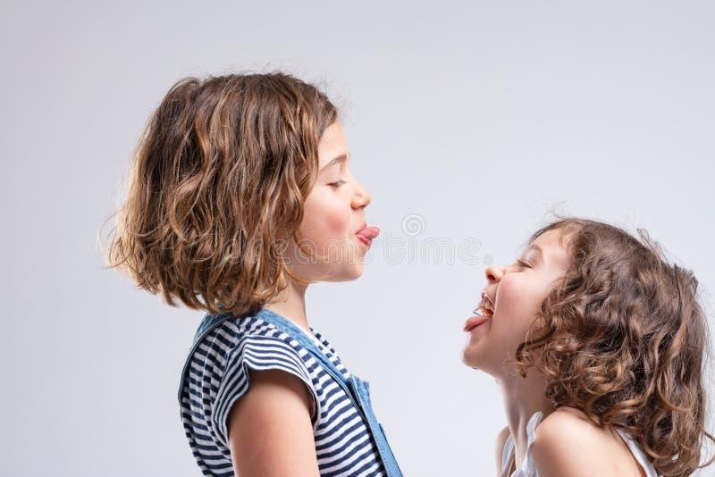 Zwei freche junge Mädchen, die heraus ihre Zungen haften stockfoto