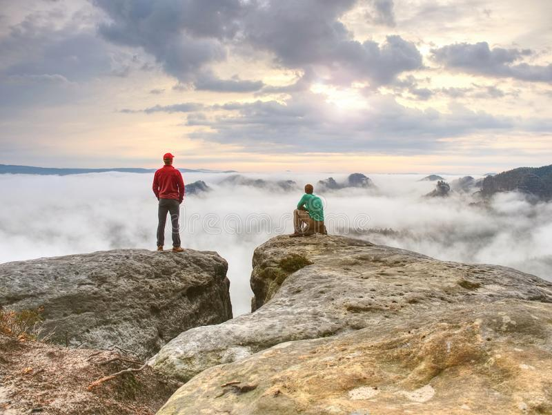 Zwei Freunde, das Wandererdenken und der Fotoenthusiast macht Fotos des Falles lizenzfreie stockbilder