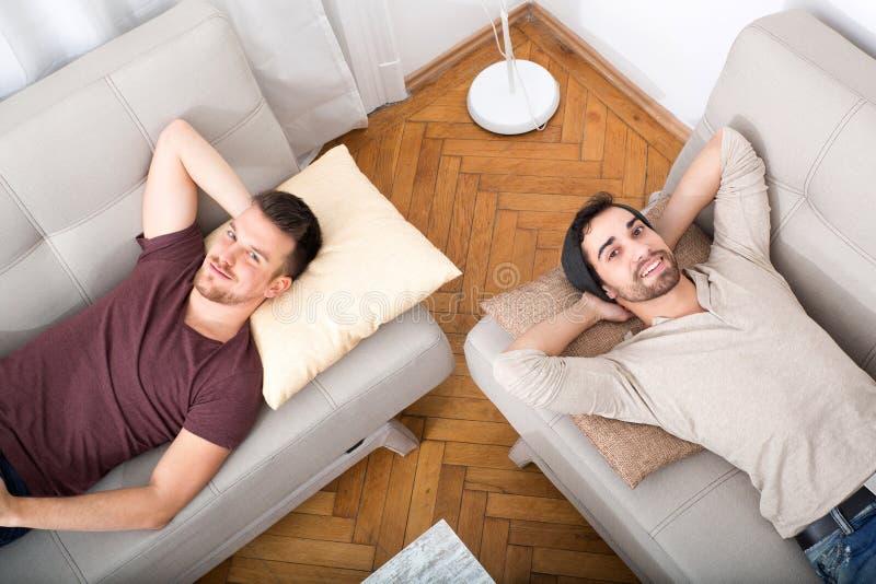 Zwei Freunde, die auf dem Sofa sich entspannen stockfoto