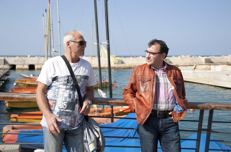 Zwei Freunde, die auf der Ufergegend vor dem hintergrund der Boote sprechen lizenzfreie stockbilder