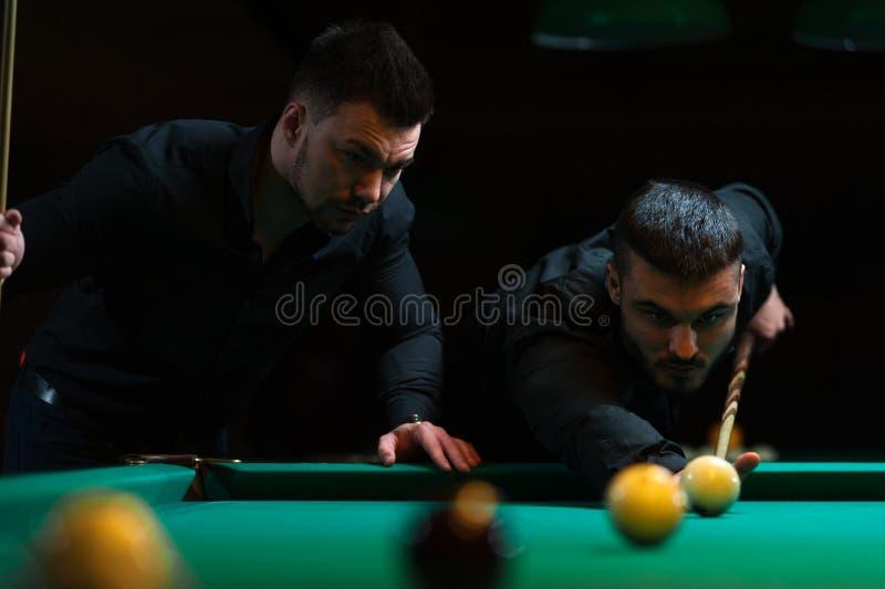 Zwei Freunde, die den Spaß spielt Snooker haben lizenzfreies stockfoto