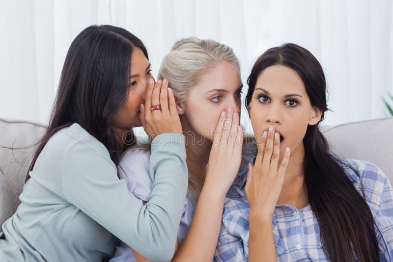 Zwei Freunde, die Geheimnis zu entsetztem Brunette flüstern lizenzfreies stockfoto
