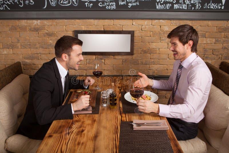 Zwei Freunde, die im Café sitzen und das Mittagessen essen stockfotografie