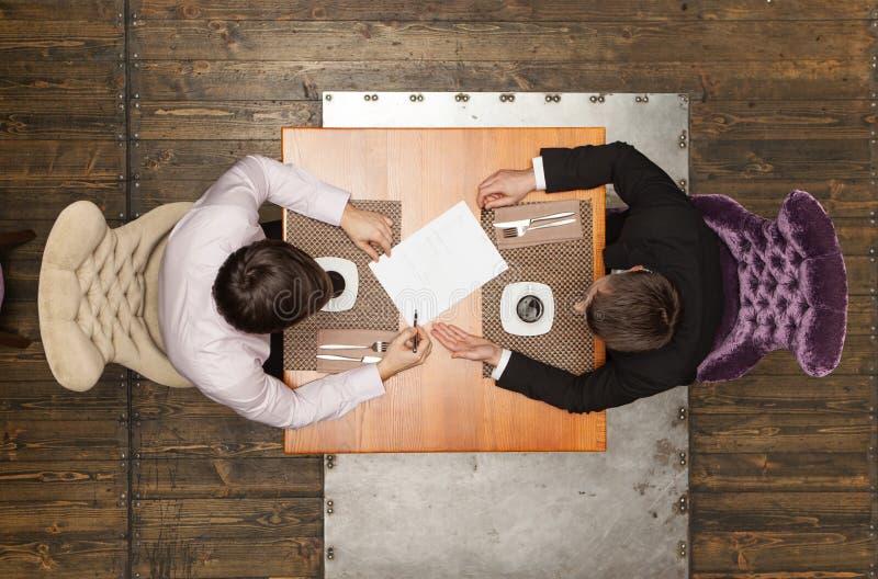 Zwei Freunde, die im Café sitzen und das Mittagessen essen stockbilder