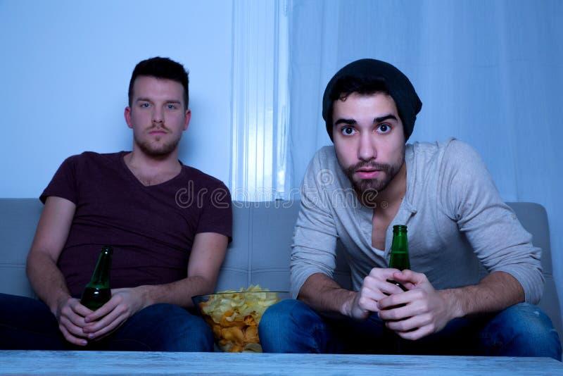 Zwei Freunde, die leidenschaftlich mit Bier und Chips fernsehen lizenzfreies stockfoto