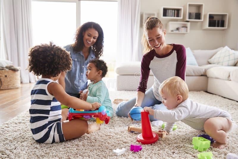 Zwei Freunde, die mit Kleinkind spielen, scherzt auf Wohnzimmerboden stockbild