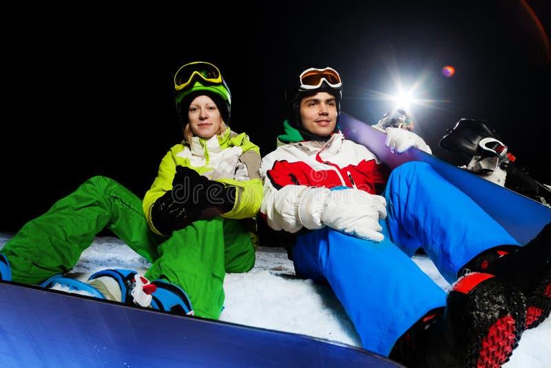 Zwei Freunde, die mit Snowboards nachts sitzen lizenzfreie stockfotografie