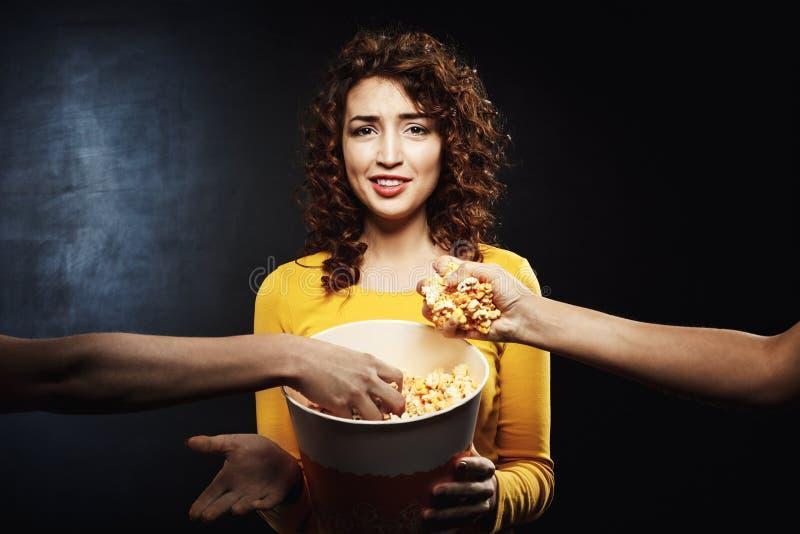 Zwei Freunde, die Popcorn von Mädchen ` s Eimer nehmen Negative Gesichtsgefühle lizenzfreies stockfoto