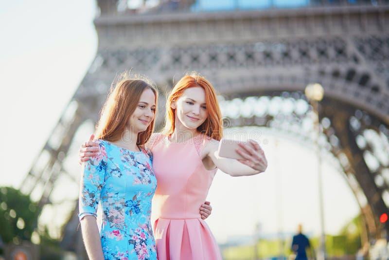 Zwei Freunde, die selfie nahe Eiffelturm in Paris, Frankreich nehmen stockfotos
