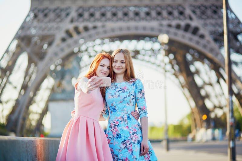 Zwei Freunde, die selfie nahe Eiffelturm in Paris, Frankreich nehmen stockbilder