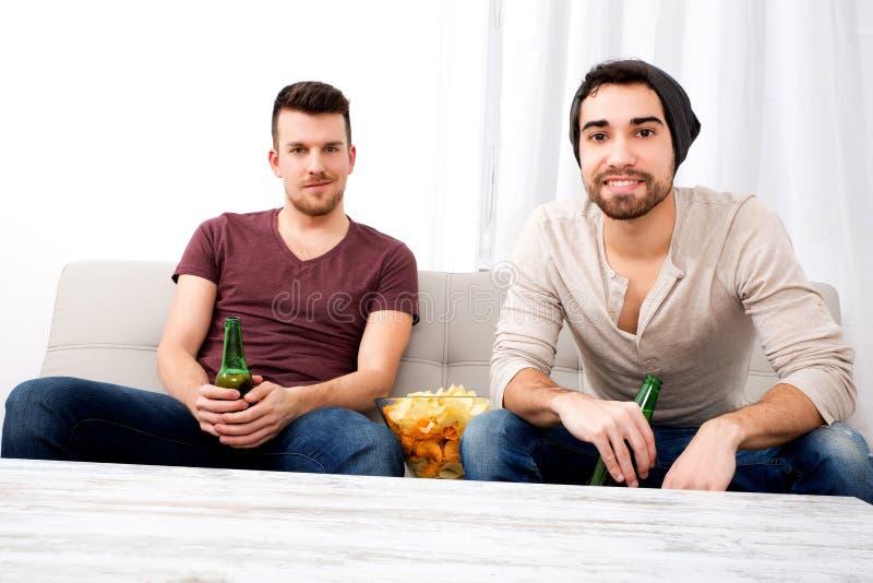 Zwei Freunde, die zu Hause fernsehen stockfotografie